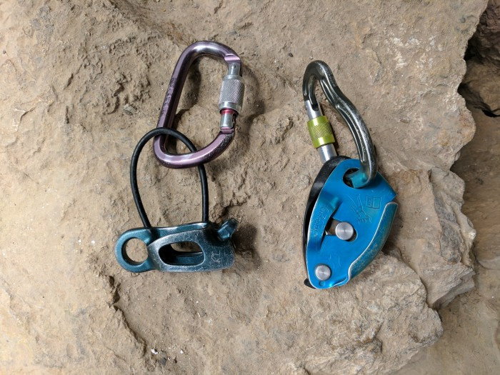 A Black Diamond ATC-XP belay device next to a Petzl Grigri 2 belay device