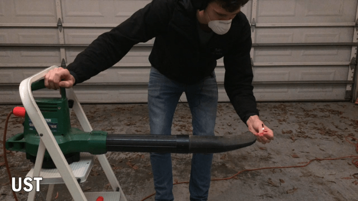 A UST stormproof match remaining lit in front of a leaf blower