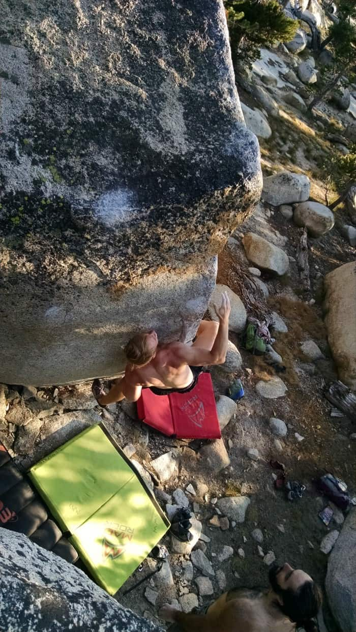 A climber bouldering above two Mad Roch Mad Pad crash pads