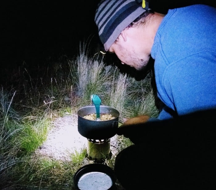 Cooking a camp meal by headlamp.