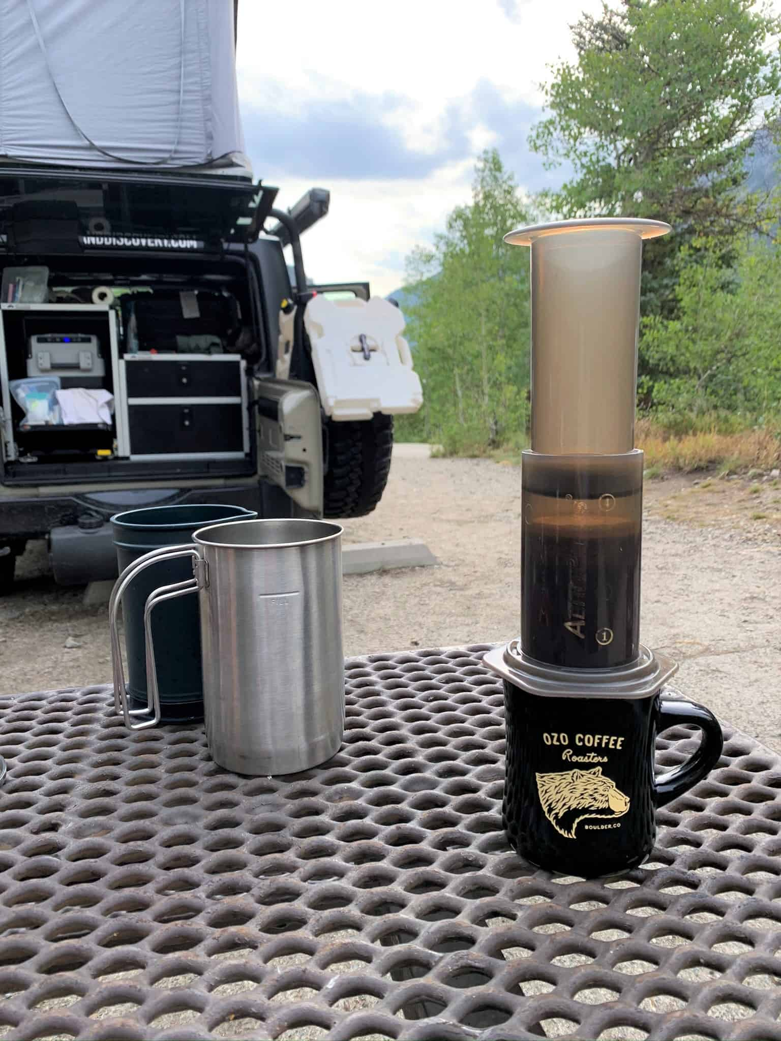 The AeroPress coffee maker brewing a cup of coffee at a campsite with a Jeep camper and some trees in the background